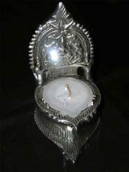 """Diya - This is brass metal made diya. Image of godess laxmi engraved on top of brass diya. This is 4.5"""" is length and about 250 gm in weight."""