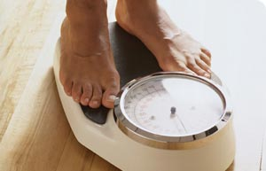 Feet on Scales - A person standing on scales, most likely weighing themselves or posing for this photo.