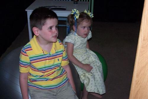 Children sitting on exercise balls - Children sitting on exercise balls and watching tv.