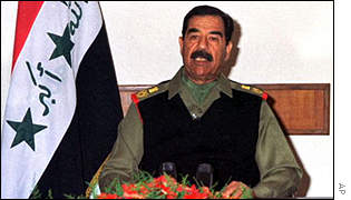 Saddam Hussein the ex-President of Iraq - Saddam Hussein beside the national flag of Iraq.