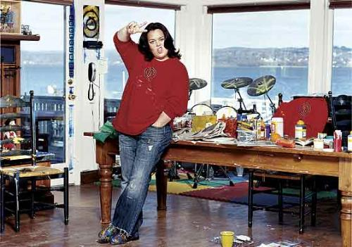 "Rosie O'Donell in her studio. - I love this photo of Rosie. When I imagine the Rosie that I think I know. This is her. The woman on TV is acting a part. The view is spectacular. The studio's a mess yet fabulous. Did you notice the drumset in the corner? Rosie making the ""peace out"" sign. She looks happy. What a life...sigh."