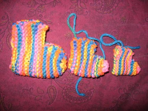 Rainbow booties. - Making a pattern for booties. The tiny one was made on size 3 needles, the next one on size 6's from the same pattern. Then I tossed that pattern, wrote my own pattern, and made the third one.
