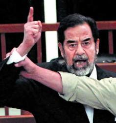 Is Saddam Hussein's Death Sentence Justifiable? - The former Iraqi President, Saddam Hussein, yells at the court on Sunday as the hand of a bailiff attempts to restrain him. The High Tribunal found the Iraqi leader guilty of crimes against humanity and sentenced him to death by hanging