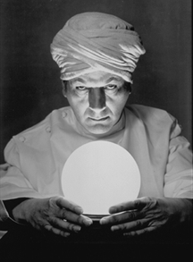 Futurists - The man is scrying to help him percieve his psychic abilities . the crystal ball helps him see the past,present and future. The looks of him arouse a question of his authenticity.