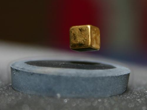 Magnets and superconductors - This is a photo of a cubical magnet levitating over a superconduting material.