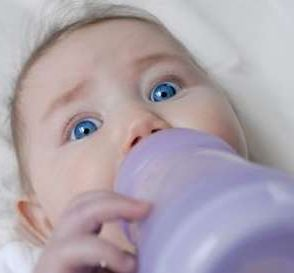 Help, I need more food! - Baby holding a milk bottle.