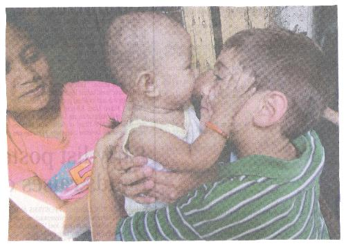 Doing a good deed for others - Photo shows a young philanthropist cuddling a baby.