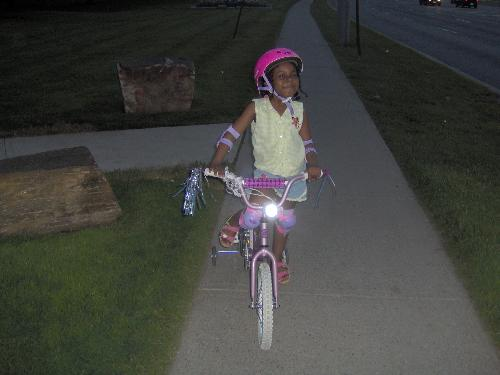little girl on bicycle -  This is summer night just after having fun for hours riding through the neighbourhood.