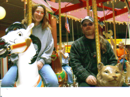 Riding the carousel in Seaside Oregon - This is my hubby and I riding the carousel