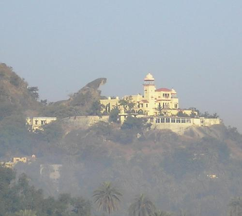 Nature Created and Man-made structures - Juxtaposing man-made palace and the mature created toad-rock, through the fog, in the morning time! This looks like a palace with its protector!