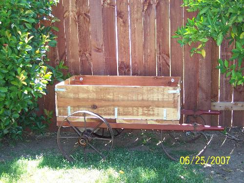 My flower cart my husband made me - The flower cart was made by my husband the wheels are antique wheels from an old cart which held tanks for wielding. He build the box and added the handles.
