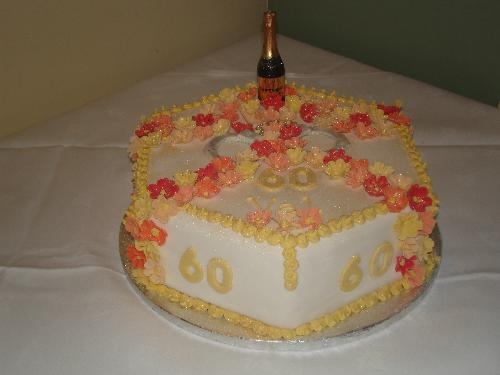 The Cake - Val's 60th Birthday Cake. Autumn coloured flowers, champagne candle and handcuffs. lol