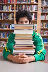 college kid with books - picture of a college semi-hot guy with tons of books in the library