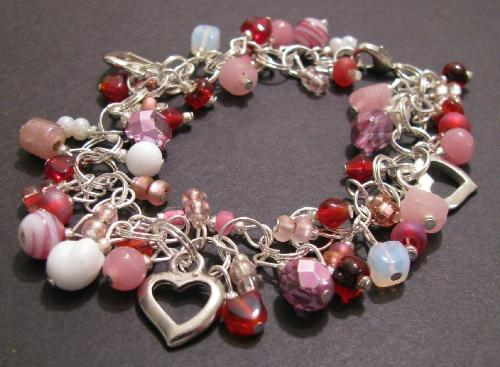"""Valentine Sweetheart Bracelet - Made with sterling plated rings, this gorgeous charm style bracelet measures 7 1/2"""" in length, w/ a lobster clasp. The bracelet is adorned with various glass beads in reds, pinks and white and has3 silver heart charms. A wonderful gift for any sweetheart on Valentine's Day (or just a little something special for yourself!) SOLD"""
