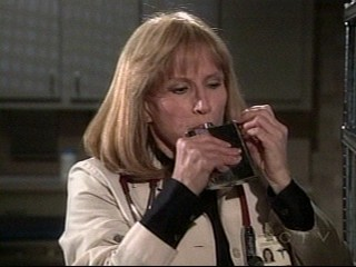 Screencap of GH's Monica Quartermaine - Picture of dear old Dr. Monica Queartermaine (Leslie Charleson) on General Hospital. She is taking a drink on the sly and keeps her stash in the Emergency Room supply room!