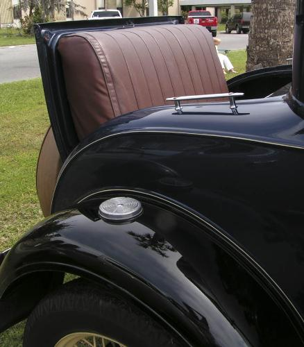 """rumble seat - Cars in the 20's had """"back seats"""" located where trunks are now. Anyone who rode in the rumble seat caught the wind, weather and exhaust from the car. They were popular, though. Photo taken at an antique car show."""