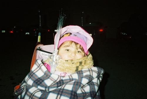 new years eve watching fireworks - Picture of girl bundled up in big flannel blanket with head peeking out in pink stroller in the cold