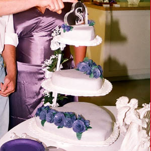 wedding cake - Triple floating hearts covered in violet fondant with dark purple fondant roses.