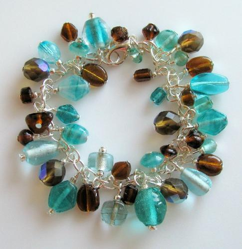Waterfall Bracelet - This 7 1/2' silver plated charm-style bracelet is adorned with an assortment of glass beads in aqua blues and browns. There are 5 czech fire polished faceted beads in light brown, that pick up the aqua blues well. A great color combo for fall! Avaailable in my Etsy.com shop.