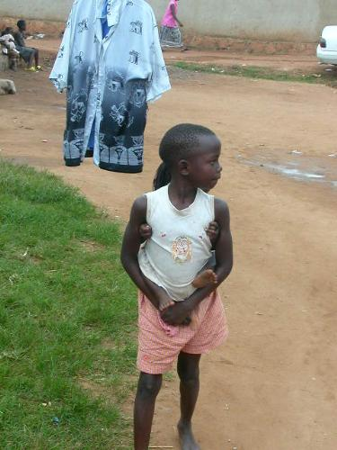 girl lifting her sister as she sells shirt behind. - Girl sported selling shirt while at the same time attending to her young sister at back.