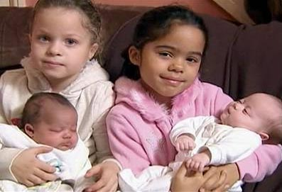 Two black two white twins - The elder twins are holding their younger twins.