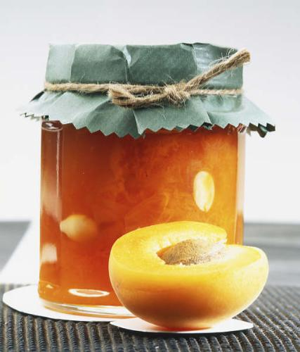 Jar of apricot jam - Delicious apricot jam made to be a gift for grandmother. The jam is made of fresh apricots and lots of sugar, aged for some time so everything soaks together. To make it look like a present, tie a nice ribbon on jar's lid.