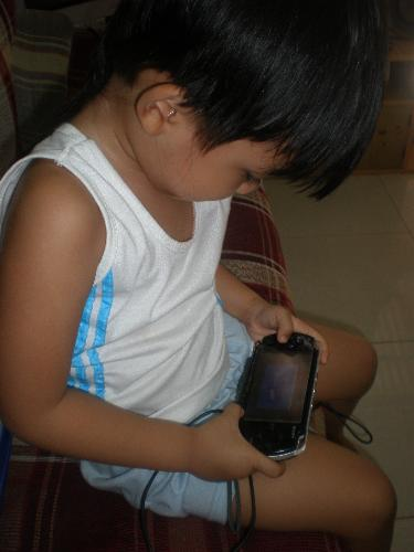 Addicted with PSP - My son playing his favorite game in his PSP.