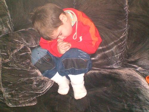 My son after he fell asleep on the couch - This is my son he fell asleep on the couch after I sat him there, so i could get his snowsuit on to go out.