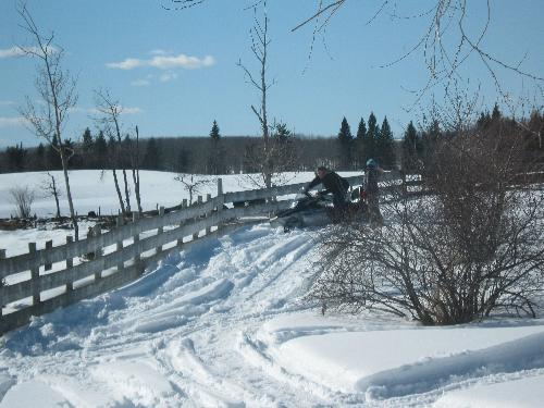 Stuck again - My dad out getting my sister and the snowmobile unstuck again.