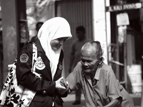 a lady helping an old woman - the old lady must have been too weak to stand up by herself; the good woman was kind enough to help her up.