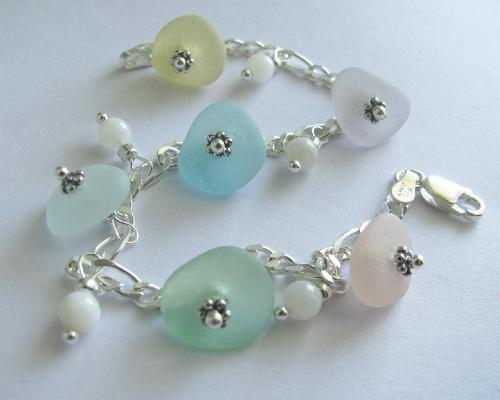 Rainbow Sea Glass Bracelet - Six pieces of sea glass adorn this 7 1/2' sterling silver bracelet. The bracelet is accented with mother of pearl polished shell beads. The colors of sea glass in this bracelet are yellow, lavender, aqua blue, white, seafoam green & pink.