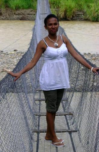 YOung lass of PNG crossing a wire bridge - Modern young lass crossing over a tradtional wire bridge in a rural PNG.
