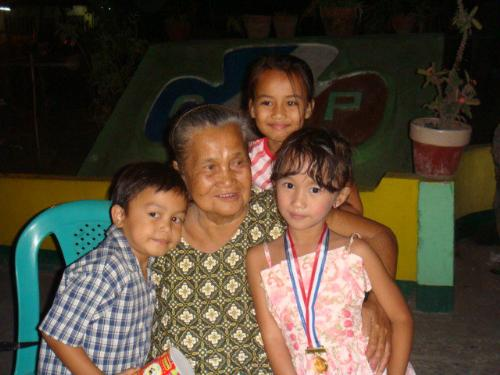 My Grandmother - This is my loving Grandmother. she's the best story teller. i love her. at the picture, she's with my cousins. mico, lei, and angelica. this picture was taken at angelica and mico's preparatory graduation, where angelica got the highest achievement in their class.