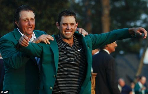 Charl Schwartzel - Green King: Former champion Phil Mickelson helps 2011 winner Charl Schwartzel into the famous green jacket.