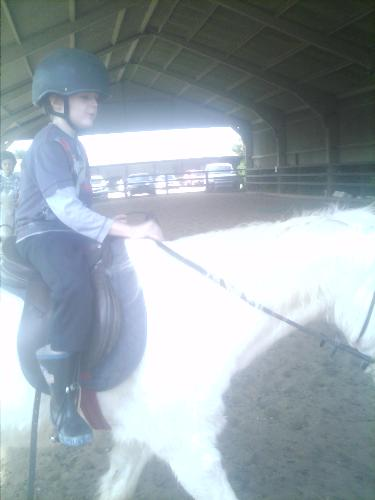 Older son looking on while riding - Here is my son on his own, walking around the court with the horse.