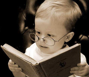 Reading Child - A young child with glasses reading.
