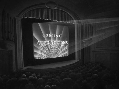 Movie Theater - Black and white photo showing the inside of a movie theater with 'Coming attractions' on the screen.