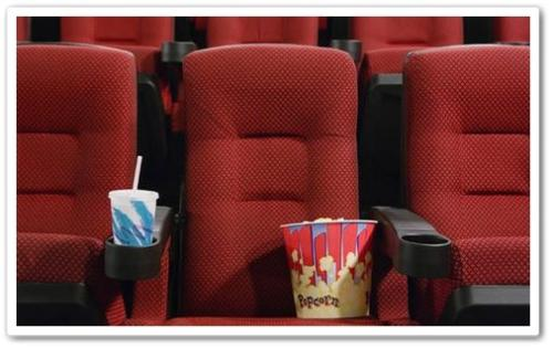 Movie Theater  - A picture of a seat with a drink and popcorn.