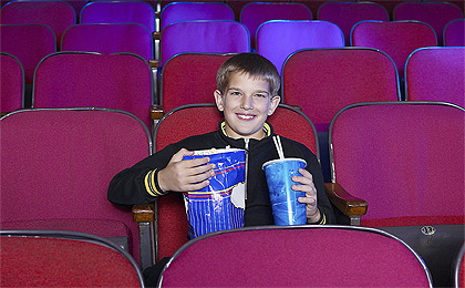 Watching A Movie - A boy in a movie theater alone and holding a large drink and popcorn.