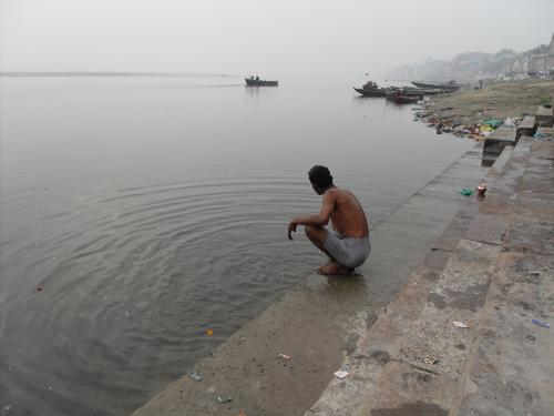 apathy - This is a photo of a man sitting alongside the bank of the river ganges and u can c the garbage pile on the sides of the bank of the river even though it is considered sacred.