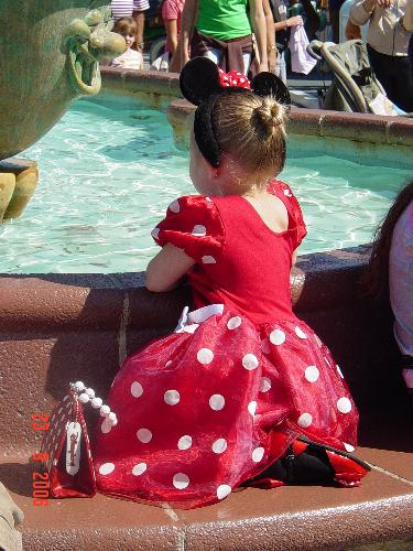 My daughter at Disneyland - A few years back we took both our kids to Disneyland. I had my daughter dressed as Minnie and my son dressed as Mickey. She was looking in the Mickey fountain just enjoying the sound of the water and coolness of it. I thought it was precious.