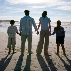 family life - an image of a family standing on a beach for this category