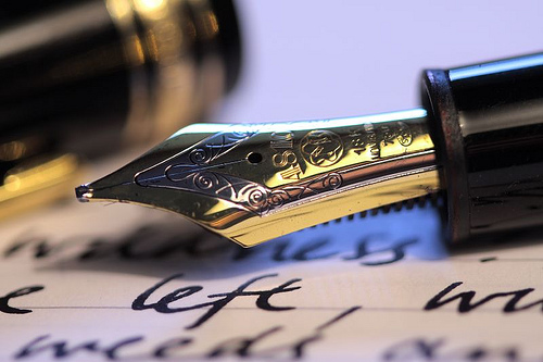 Fountain Pen Writing - A tradition fountain pen above a page of sample writing. The old-fashioned way of putting ideas to paper.