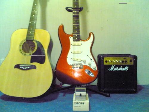 guitars - A wood guitar and a red guitar plus speaker box.