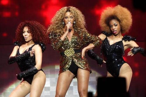 Beyonce - Beyonce and two of her back up singers in concert. Beyonce in hot pants and golden jacket. So her.