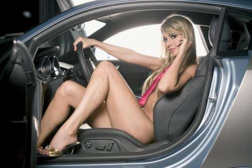 In a car - A beautiful woman showing off a car.