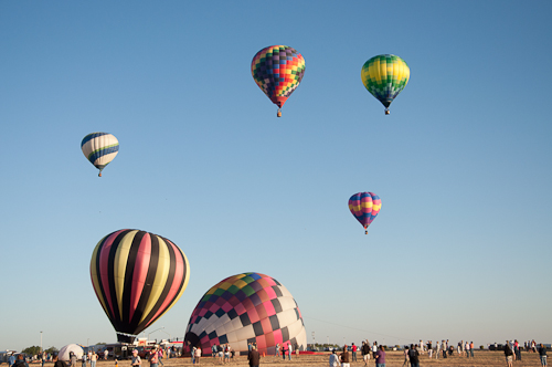 There they go! - Four hot air balloons drift away on the wind.