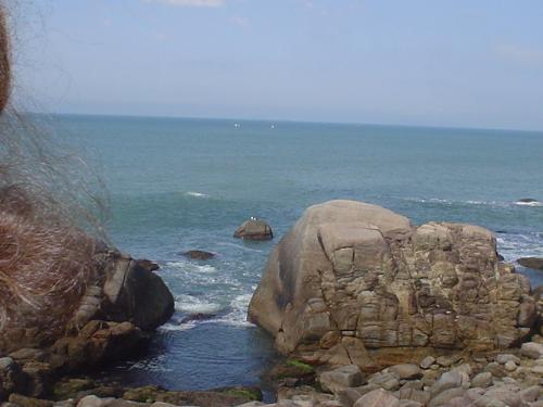 A view near Bombinhas beach, Santa Catarina - The Atlantic Ocean is showing its majesty as well as the huge boulders.