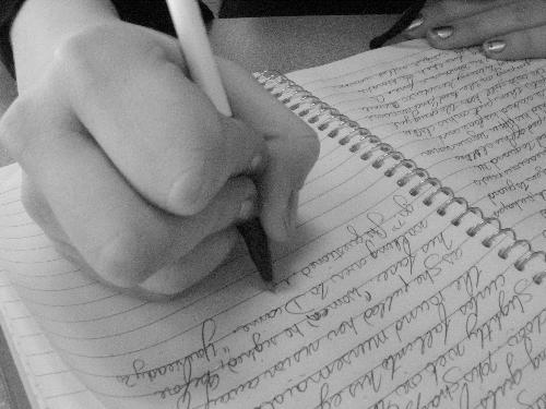 Writing - Someone writing in a notebook.