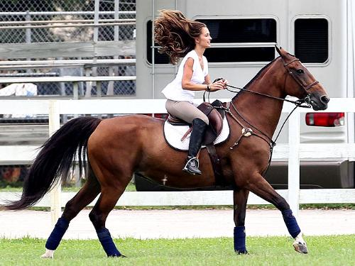 Minka Kelly - Her riding looks awlful! She is to far back in the saddle. Her legs need to be straight and heels down! Looks like she has the reins in one hand pulling on horses mouth! The horse doesn't very happy!